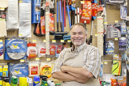 hardware store: Portrait of a happy mature salesperson with arms crossed in hardware store