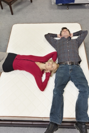 furniture store: Friends lying on mattress with hands behind head in furniture store