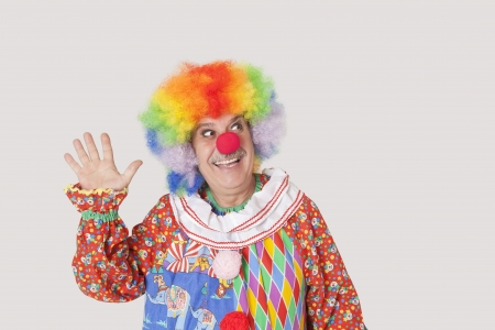 Cheerful senior male clown waving hand while looking away over gray background Stock Photo