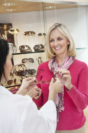 Happy senior woman taking glasses from optician in store Stock Photo - 20766920