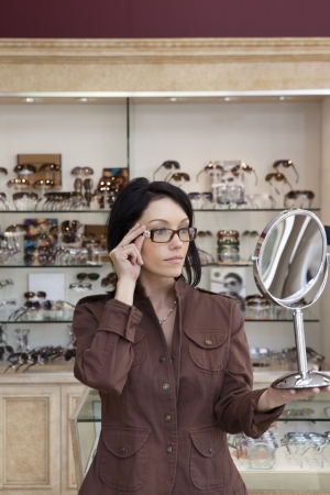 mid adult female: Beautiful mid adult female customer trying on glasses while looking into mirror