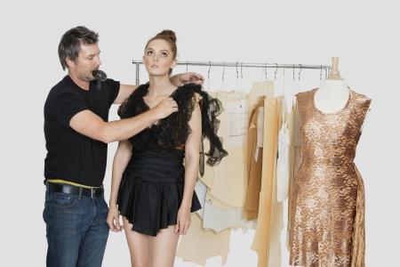 design studio: Mature male fashion designer adjusting dress on model in design studio