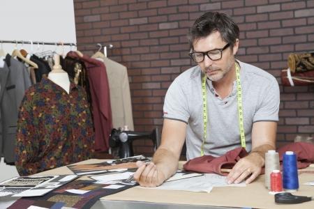 design studio: Mature male fashion designer working in design studio