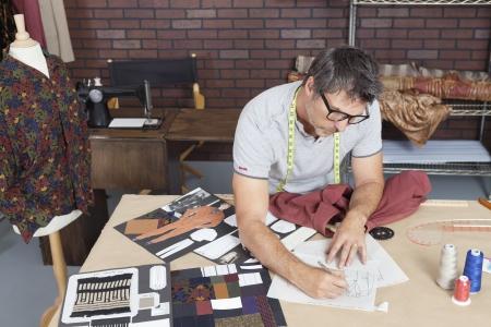 design studio: Mature male fashion designer working on sketch in design studio LANG_EVOIMAGES