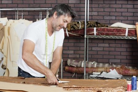 design studio: Mature male dressmaker cutting fabric in design studio