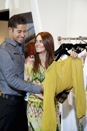 decisionmaking: Happy young couple selecting a dress together in fashion boutique