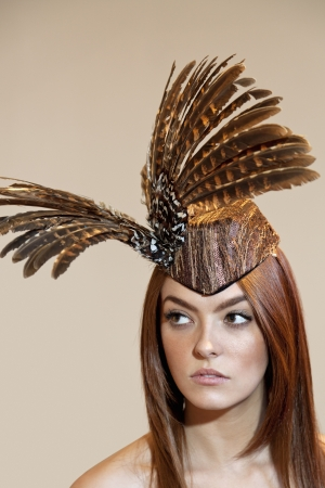 headgear: Young woman with feathered headgear looking away over colored background