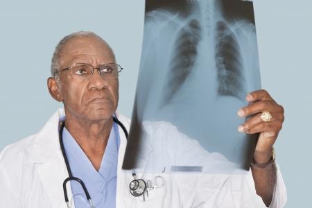80s adult: Africano-americana masculina m�dico analizar informe de rayos x sobre fondo azul claro LANG_EVOIMAGES