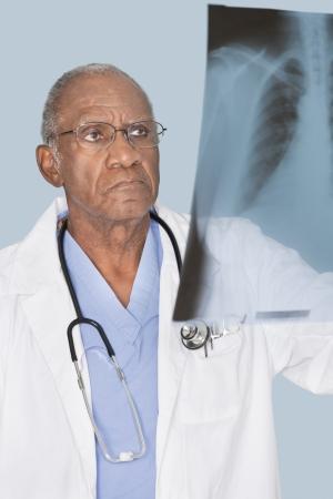 80s adult: Afroamericanos se�or doctor analizar informe de rayos x sobre fondo azul claro LANG_EVOIMAGES