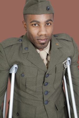health facility: Portrait of an African American US military officer with crutches over brown background