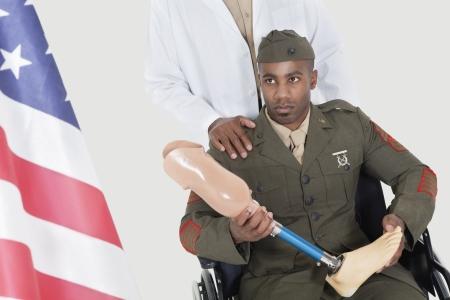80s adult: Doctor con el oficial militar discapacitado celebraci�n miembro artificial mientras mira a la bandera americana