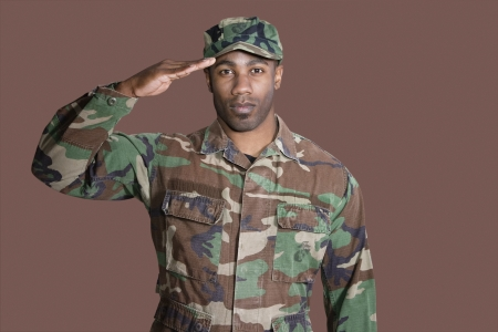 army man: Portrait of a young African American US Marine Corps soldier saluting over brown background