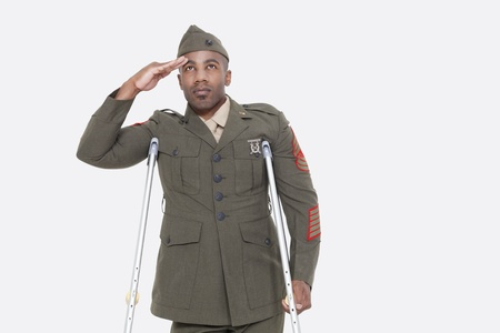 health facility: Disabled African American military officer in uniform salutes over gray background LANG_EVOIMAGES