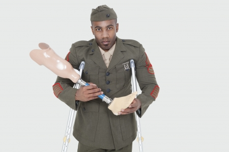 health facility: Portrait of a disabled US military officer holding prosthesis leg over gray background
