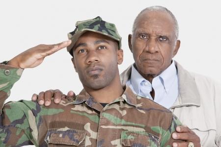 80s adult: Retrato de EE.UU. Cuerpo de Marines de soldado con el padre saludando sobre fondo gris LANG_EVOIMAGES