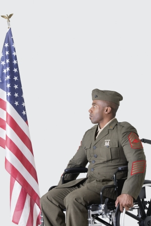 health facility: Young US soldier in wheelchair looking at American flag over gray background