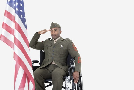 health facility: Young US soldier in wheelchair saluting American flag over gray background