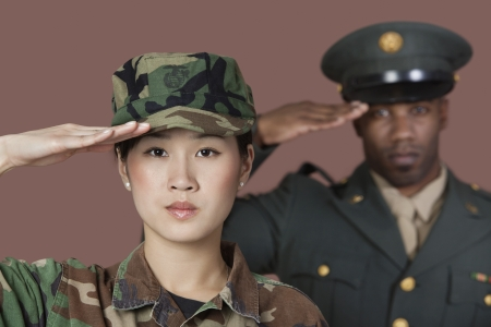 us soldier: Close-up portrait of young female US Marine Corps soldier with male officer saluting over brown background