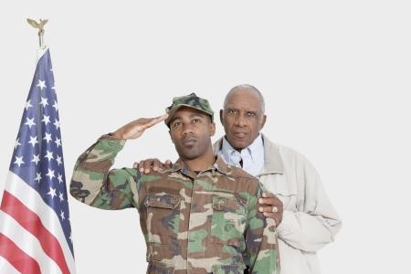 80s adult: Retrato del padre con el Cuerpo de Marines de EE.UU. soldado saludando bandera estadounidense sobre fondo gris
