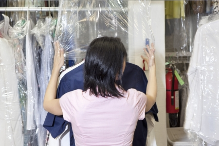 dry cleaned: Vista posteriore di un dipendente di et� media, mettendo in plastica sul asciutti puliti i vestiti