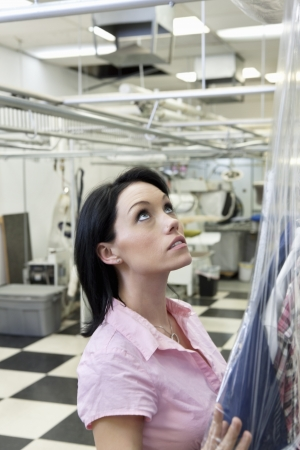 dry cleaned: Beautiful mid adult woman putting plastic to dry cleaned while looking up LANG_EVOIMAGES