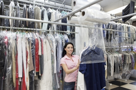 dry cleaned: Portrait of a happy mid adult woman putting plastic to dry cleaned clothes in laundry