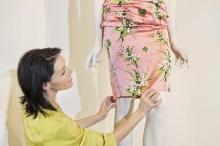 Schöne mittlere erwachsene Frau Anpassung Kleid auf Schaufensterpuppe im Modegeschäft