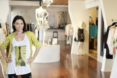 floo: Portrait of a happy mid adult woman standing with hands on hips in fashion clothing store LANG_EVOIMAGES