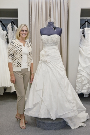 decisionmaking: Portrait of a happy woman standing by elegant bridal dress in boutique