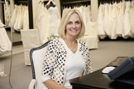 fem: Portrait of a happy senior woman sitting in bridal store LANG_EVOIMAGES