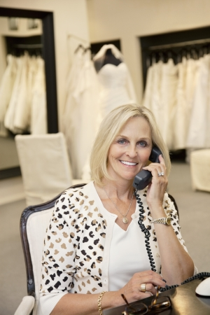 fem: Portrait of a happy woman listening to telephone receiver in bridal store LANG_EVOIMAGES