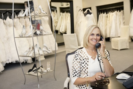 fem: Portrait of a happy woman making a call in bridal store