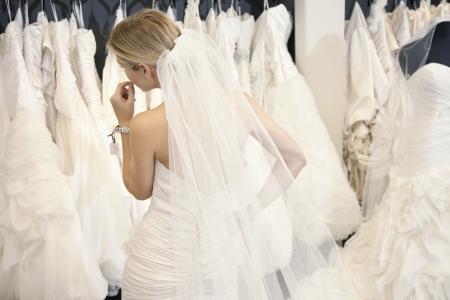 ブティックのディスプレイ上のブライダル ガウンを見てウェディング ドレスの若い女性の背面図 写真素材