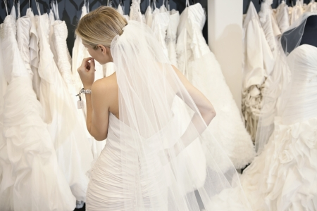 customs and celebrations: Back view of a young woman in wedding dress looking at bridal gowns on display in boutique