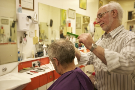 profess: Barber cutting senior mans hair in barbershop LANG_EVOIMAGES