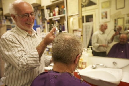 mirro: Happy man cutting senior customers hair with razor