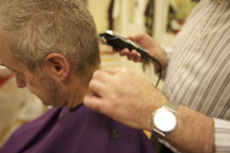 Midsection of senior barber giving haircut to customer in salon Stock Photo - 20767414