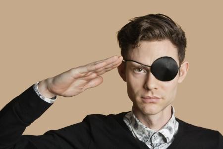 Portrait eines Mannes mit Augenklappe salutieren über farbigen Hintergrund