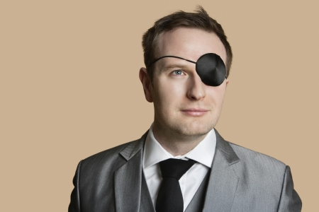 Close-up von einem jungen Geschäftsmann mit Augenklappe Wegschauen über farbigen Hintergrund