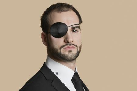 Porträt eines jungen Geschäftsmann mit Augenklappe über farbigen Hintergrund Standard-Bild