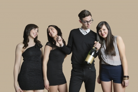 fema: Portrait of mid adult man and young females holding champagne bottle over colored background LANG_EVOIMAGES