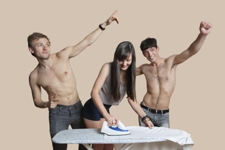 hombres sin camisa: Hombres sin camisa con camisa de plancha de la mujer sobre fondo de color