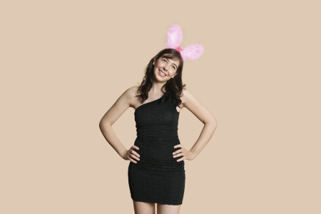 off the shoulder: Beautiful young woman in black dress with bunny ears looking away over colored background