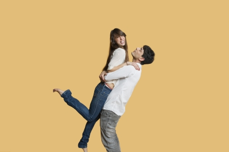 carrying girlfriend: Happy young man carrying girlfriend over colored background