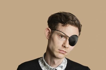 Sad Mitte erwachsenen Mann mit Augenklappe über farbigen Hintergrund