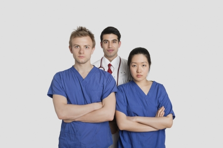profess: Portrait of confident healthcare workers standing over gray background LANG_EVOIMAGES