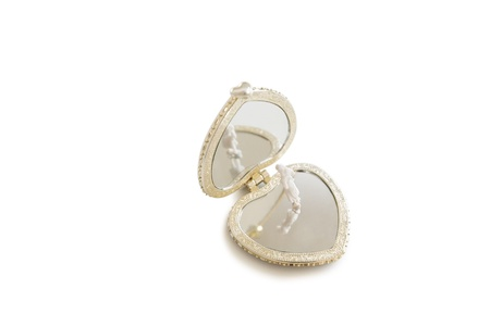 A small figurine standing on an open heart shape pendant over white background