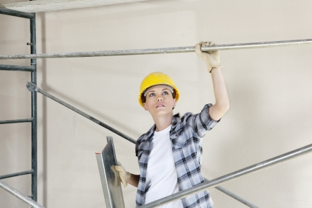 mid adult female: Mid adult female architect looking up while standing under scaffold at construction site