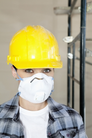 dust mask: Portrait of woman worker wearing dust mask at construction site LANG_EVOIMAGES