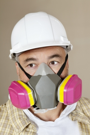 dust mask: Close-up portrait of contractor with dust mask over colored background